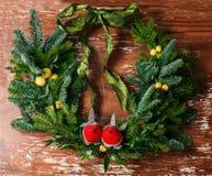 Floral διακόσμηση στεφανιών Χριστουγέννων με τα μπιχλιμπίδια, το κόκκινο τόξο, τον ελαιόπρινο και τη χειμερινή πρασινάδα πέρα από Στοκ Εικόνες