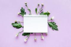 Floral πρότυπο Σημειωματάριο μεταξύ των οφθαλμών και των φύλλων στην πορφυρή τοπ άποψη υποβάθρου copyspace Στοκ Εικόνες