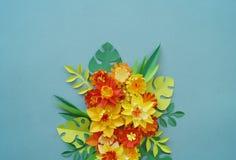 Floral ρύθμιση των λουλουδιών εγγράφου σε ένα μπλε υπόβαθρο φύλλα λουλουδιών τροπ&iota Κόκκινος, κίτρινος, πράσινος, πορτοκαλής κ Στοκ φωτογραφία με δικαίωμα ελεύθερης χρήσης