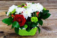 Floral ρύθμιση των φρέσκων λουλουδιών στο πράσινο ψάθινο καλάθι ο Στοκ Εικόνα