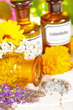Floral aromatherapy, essential oil and plant extracts. A brown glass bottle tipped on its side spilling dired crushed flower petals with fresh lavender and Stock Photos