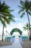 Flower altar decoration for wedding on the beach. Floral arrangement for backdrop at a wedding ceremony on the beach. Chairs and arranged on beach for wedding Stock Photos