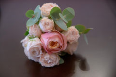 Horizontal shot of glamorous wedding bouquet featuring pink peonies and greenery positioned on a mauve glossy background. Floral arrangement, essential accessory Stock Photo