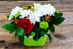Floral arrangement of fresh flowers in the green wicker basket o Stock Image