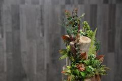 Floral arrangement of multicolored flowers, leaves and berries i. N wooden stump, floral art close-up.artificial flowers Stock Images