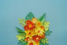 Floral arrangement of paper flowers on a blue background. tropical flowers and leaves. Red,yellow,green,orange and blue. Handmade flower. Spring,Easter Royalty Free Stock Photography