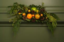 Floral Arrangement on Vintage Antique Fireplace. Holiday floral arrangement with fruits and branches on vintage antique fireplace mantel Stock Images