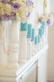 Floral arrangement with white and blue flowers and candles on candle holders. Royalty Free Stock Image