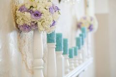 Floral arrangement with white and blue flowers and candles on candle holders. Wedding decor Stock Photos