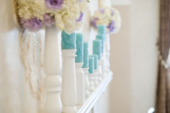 Floral arrangement with white and blue flowers and candles on candle holders. Royalty Free Stock Images