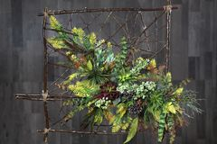 Floral arrangement on wooden frame, grey wood background. Artifi. Cial flowers Stock Image