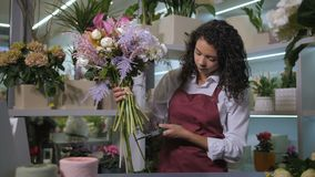 Floral artist cutting flower stems in workshop. Professional female florist completing gorgeous composition of floral bouquet cutting flower stems with pruner in stock video