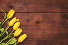 Floral background with yellow tulips over rustic wood Stock Photo