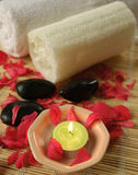 Floral bath with red rose peta. Floral bath preparations with aromatic candle, loofah, stones and flower petals Royalty Free Stock Photos