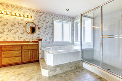 Floral bathroom with white tub and shower. Spacious bathroom with floral wallpaper, concrete floor and windows. View of white tub, glass door shower and wooden royalty free stock photos