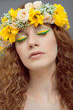 Floral beauty. Studio portrait of young beautiful woman with flowers in hair stock photo