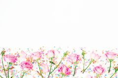 Floral border frame with pink flowers and bright candy confetti on white background. Flat lay, Top view. Roses flower texture stock photo