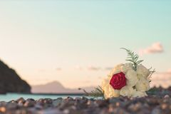 Floral Bouquet on beach at sunset. Red rose at center, white rose around it. Beautiful sky with clouds. 