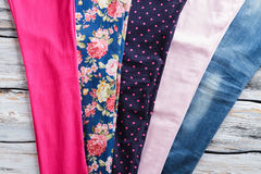 Floral and bright pink cloth. Fabric pieces on wooden background. Materials stored at clothes workshop. Custom made spring clothing Royalty Free Stock Photo