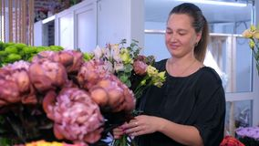 Florist woman makes big flower bouquet and talks with client in flower shop.