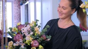 Florist woman makes big flower bouquet and smiles at camera in flower shop.