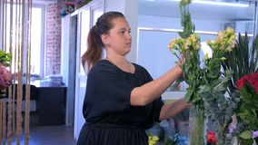 Florist woman works makes bouquet of beige eustoma in flower shop. stock footage
