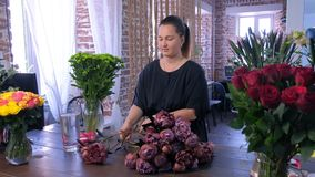 Florist woman works makes bouquet of brown maroon color peonies in flower shop. stock video footage
