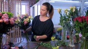 Florist creates bouquet of eucalyptus, eustoma, peony and iris in flower shop.