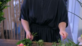 Woman florist makes a bouquet of colorful roses in flower shop, hands closeup. stock video footage