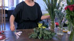 Woman florist prepares eucalyptus and iris flowers for bouquet in shop for sale.