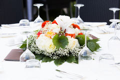 Floral centerpiece on table. Floral centerpiece for wedding banquet on white linen tablecloth set with stemware Royalty Free Stock Images