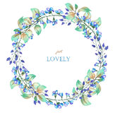A floral circle frame (wreath) of the watercolor blue flowers and green leaves, a place for a text Stock Photography