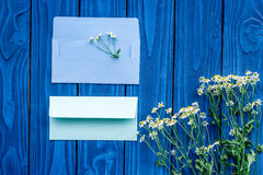 Floral composition with camomile and post card envelopes on blue wooden background flat lay mockup Stock Photo