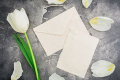 Floral composition with white tulips and paper envelope with card on dark background. Flat lay, top view. Floral pattern backgroun. Floral composition with white Stock Photos