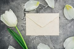 Floral composition with white tulips and paper envelope on dark background. Flat lay, top view. Floral pattern background. Floral composition with white tulips stock image