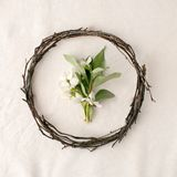 Floral composition. Wreath made of roools, leaves, and flowers on tissue white background. Rustic style of home decor, flat lay, t. Op view Stock Photos