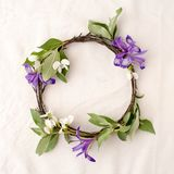 Floral composition. Wreath made of roools, leaves, and flowers on tissue white background. Rustic style of home decor, flat lay, t. Op view Royalty Free Stock Photo