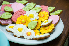 Floral cookies. Sweet flower-shaped cookies on the plate on the wooden table Royalty Free Stock Photos
