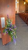 Floral cross arrangement by church door Stock Photography