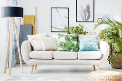 Floral cushion on beige sofa. Floral cushion on a beige sofa and posters on the wall in living room with pouf, lamp and plant stock images