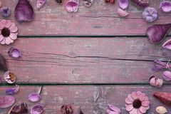 Floral decorations on pink, purple wooden desk with free space in the middle for text, photo or product presentation Stock Image