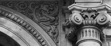 Floral dragon standing on the corner. Shot in black and white, detail on the sculpture on the facade of this historic building representing some characters / Royalty Free Stock Photo