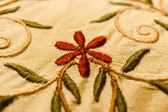 Red flower, green leaves and stems with curls, embroidered with satin stitch. Stock Photos