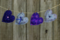 Floral fabric hearts hanging on clothesline by shabby wood background Stock Photo