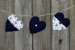 Floral fabric hearts hanging on clothesline by shabby wooden background Royalty Free Stock Images