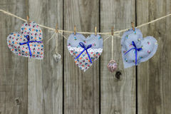 Floral fabric hearts and heart-shaped locks hanging on clothesline by rustic wooden fence Stock Photo