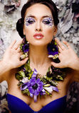 Floral face art with anemone in jewelry, sensual young brunette woman Stock Photo