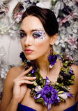 Floral face art with anemone in jewelry, sensual young brunette woman Stock Photography