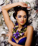 Floral face art with anemone in jewelry, sensual young brunette woman Stock Image