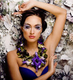 Floral face art with anemone in jewelry, sensual young brunette woman Royalty Free Stock Photography